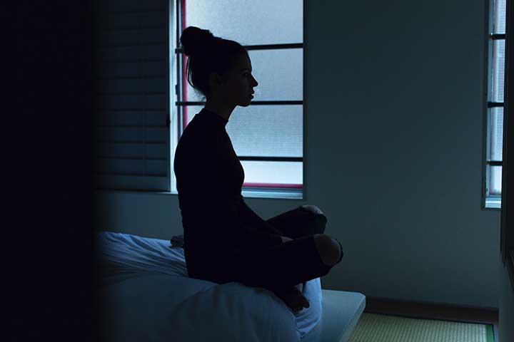 ragazza su letto affetta da ansia e insonnia