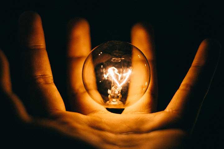 paura di perdere il controllo rappresentata da una lampadina accesa in un palmo di mano