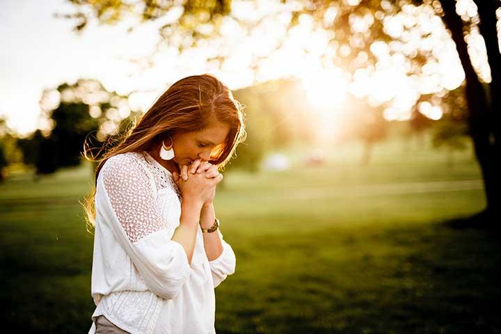 donna con mani incrociate intenta a pregare e affetta da DOC religioso