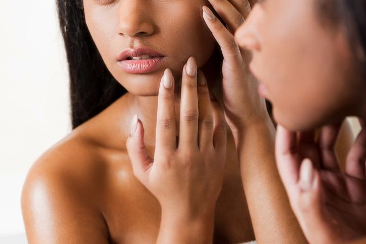 donna con dermatillomania pizzica la pelle del volto