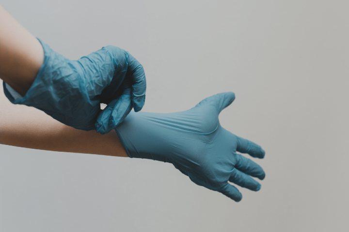 persona con doc da pulizia indossa i guanti