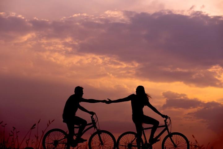 coppia in bicicletta stringe mano per paura di perdere l'altro